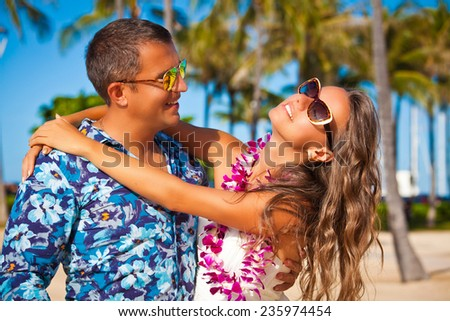 Shot of young couple enjoying beach getaway. Couple in love, summer luxury vacation in Hawaii. Travel holidays concept. - stock photo