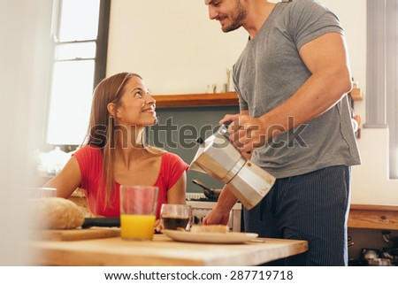 Shot of young couple having breakfast in kitchen. Young man standing and serving coffee with woman sitting by breakfast table at home in domestic kitchen. - stock photo