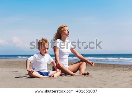 Shot of young mother with her son working out on the beach