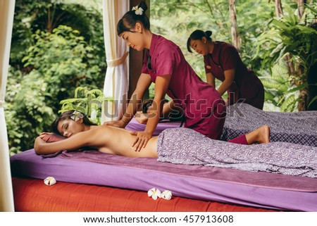 Shot of young people at outdoor spa and getting body massage at resort. Couple having back massage at luxury resort spa center. - stock photo