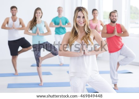 Shot of young woman instructing a group in pilates class