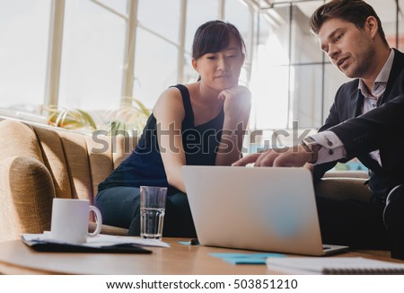 Shot of young woman sitting with businessman pointing at laptop screen. Business partners working together on laptop in office.