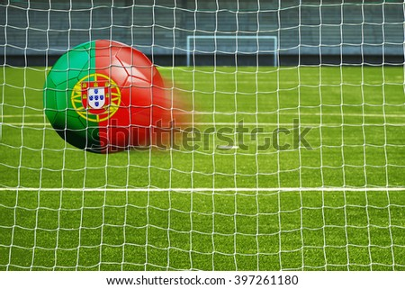Shot on goal, soccer ball with the flag of Portugal in the net  - stock photo