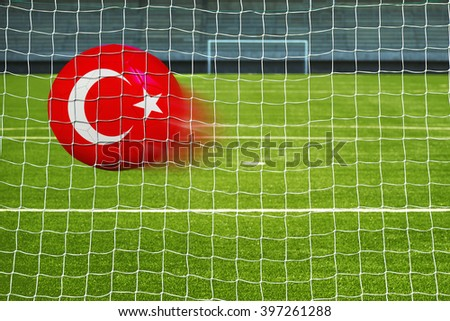 Shot on goal, soccer ball with the flag of Turkey in the net  - stock photo