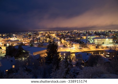 Shot over the Reykjavik area at christmas time, covered in snow with christmas lights and pine trees - stock photo