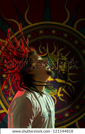 Shot portrait of a young rastaman with his dreadlocks in motion - stock photo
