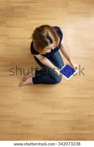 Shot taken from above of a beautiful woman sitting on the floor using her tablet computer