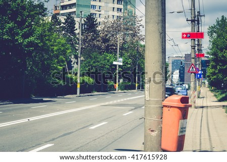 Shot to a street with low traffic with a building in the background and a dumpster in the foreground - stock photo