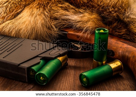 Shotgun lying next to the animal's fur produced and magazine with green cartridges 12 gauge. View close-up, focus on the shotgun - stock photo