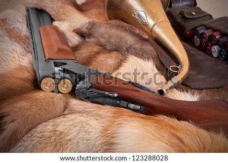 Shotgun on background of the fur - stock photo