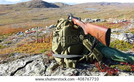 shotgun resting on green backpack with freshly hunted grouse birds in hunting net bag - stock photo