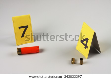 shotgun shell marked as evidence on grey