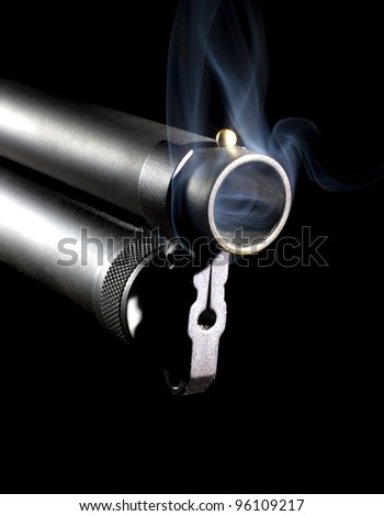 Shotgun that is hot enough to have smoke coming from the muzzle - stock photo