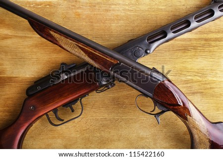 shotgun with assault rifle on wood - stock photo