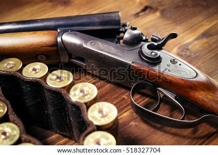 Shotgun with shells on wooden background