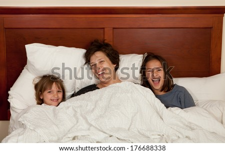 Shots of a mother and her two daughters waking up in bed with white linens part of a series