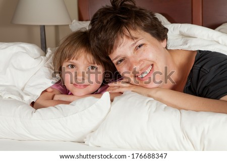 Shots of a mother  daughters waking up in bed with white linens part of a series