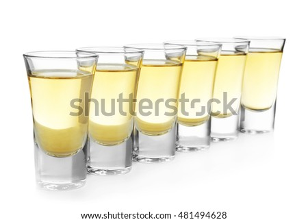 Shots of gold tequila in row isolated on white