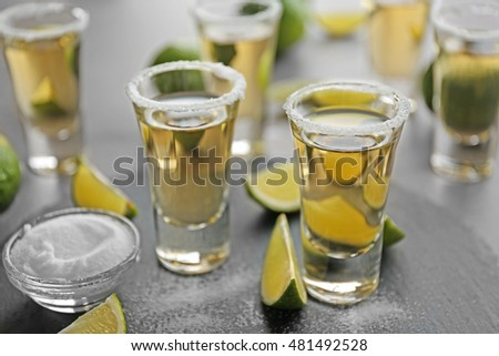 Shots of gold tequila with lime slices and salt on a tray