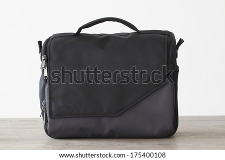 Shoulder canvas camera on wooden table - stock photo