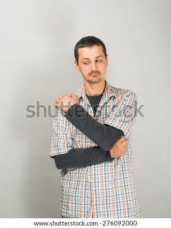 Shoulder pain. Adult man holding his painful shoulder. - stock photo