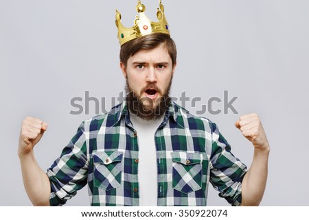 Shouting bearded man, wearing on white t-shirt, blue checked shirt and golden crown, posing on white background, in studio, waist up - stock photo