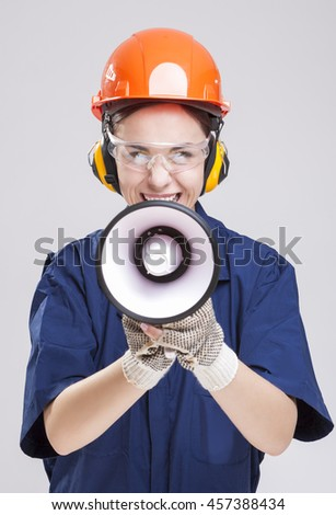 Shouting Caucasian Female Worker Posing with Megaphone and Wearing Hardhat for Protection. Vertical Image Composition - stock photo