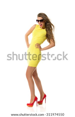 Shouting fashion model in fitted yellow mini dress and red high heels. Full length studio shot isolated on white. - stock photo