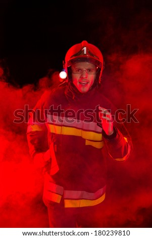 Shouting fireman in red helmet walking in smoke and holding axe. Three quarter length studio shot on black background. - stock photo