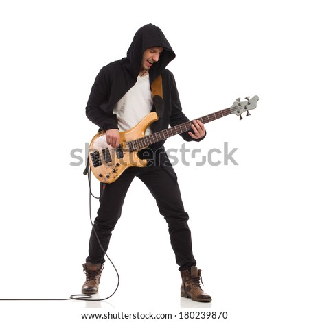 Shouting guitarist in black hoodie plays the bass guitar. Full length studio shot isolated on white.