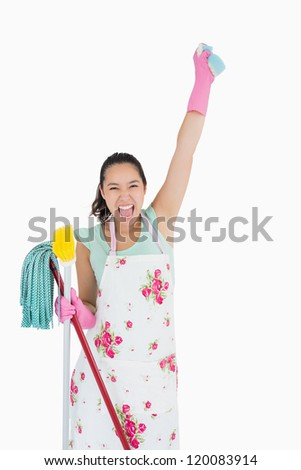 Shouting woman holding lot of cleaning tools and a sponge in the air - stock photo