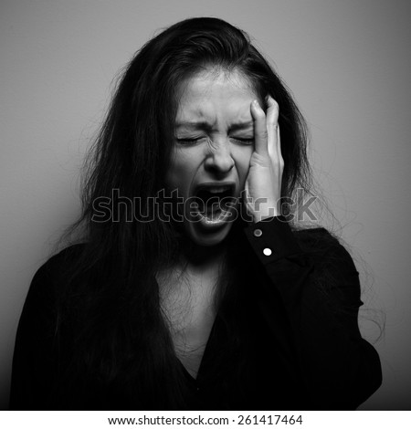 Shouting woman with unhappy, depressed crying face in big grief. Black and white portrait - stock photo