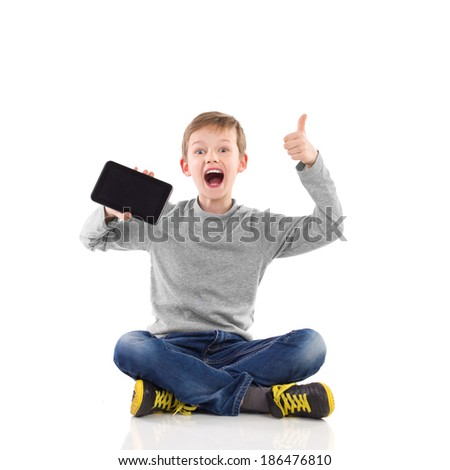 Shouting young boy sitting on the floor with legs crossed, showing tablet and giving thumb. Full length studio shot isolated on white. - stock photo