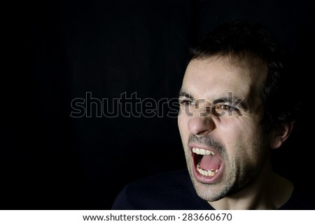 shouting young man, black background