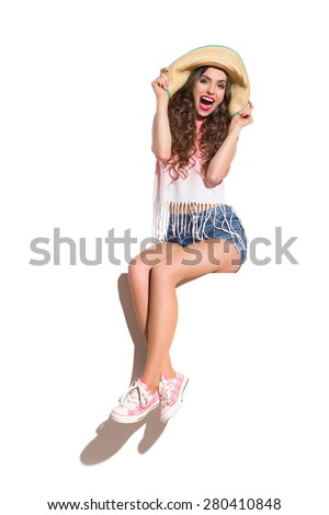 Shouting young woman in straw hat, pink top, jeans shorts and pink sneakers sitting on the white banner. Full length studio shot isolated on white. - stock photo
