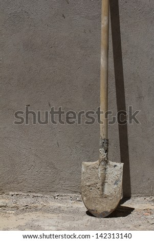 shovel against the concrete wall - stock photo