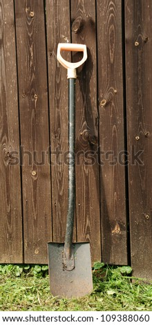 Shovel against wooden wall - stock photo