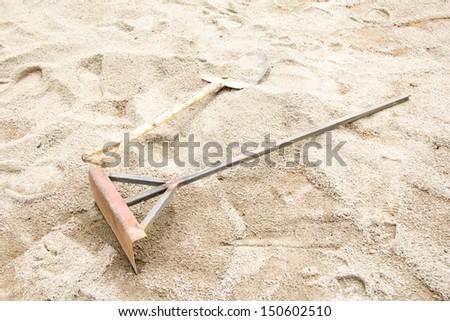 Shovel and Harrow on the sand - stock photo