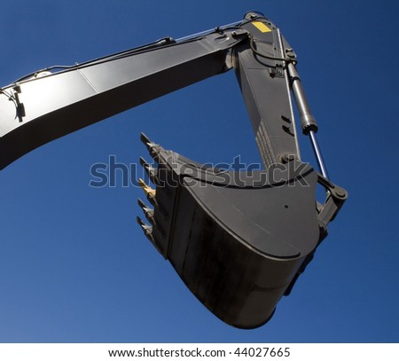 Shovel bucket against blue sky - stock photo