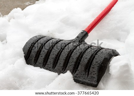 Shovel laying down against the snow. - stock photo