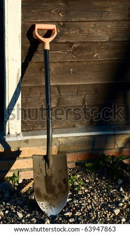 Shovel Leaning Against Wood Wall - stock photo