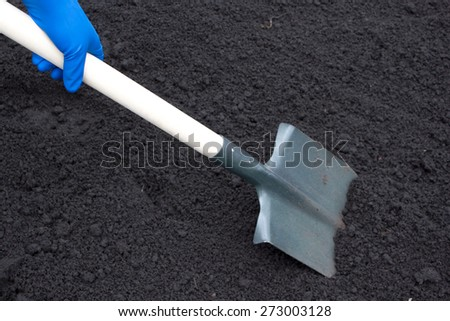 Shovel on field, digging hole with spade in field - stock photo