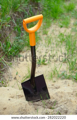 Shovel on heap of sand - stock photo