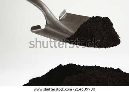 Shovel with dirt on white background up close - stock photo