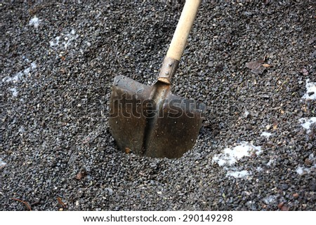 shovel with wooden handle in gravel - stock photo