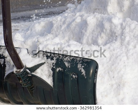 Shoveling A Snowy Driveway Fresh Snow Removal Background - Closeup snow shovel removing snow from a driveway, white winter shoveling snow pile background photo. - stock photo