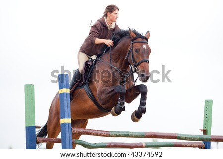show jumping in rain - young girl and horse - stock photo