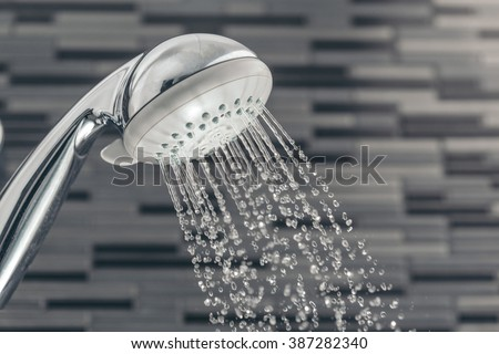 Shower head with water drops falling on a bathroom - stock photo