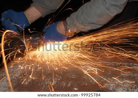 Shower of orange sparks from a worker grinding steel