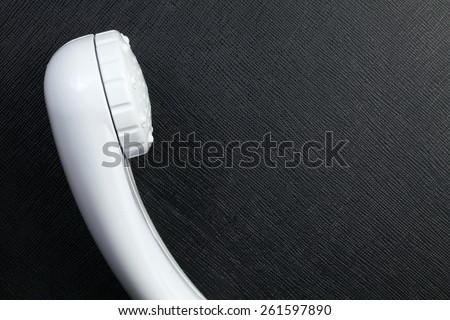 Showerhead plastic made in white color put on the black color leather background represent the bathroom equipment concept related idea. - stock photo
